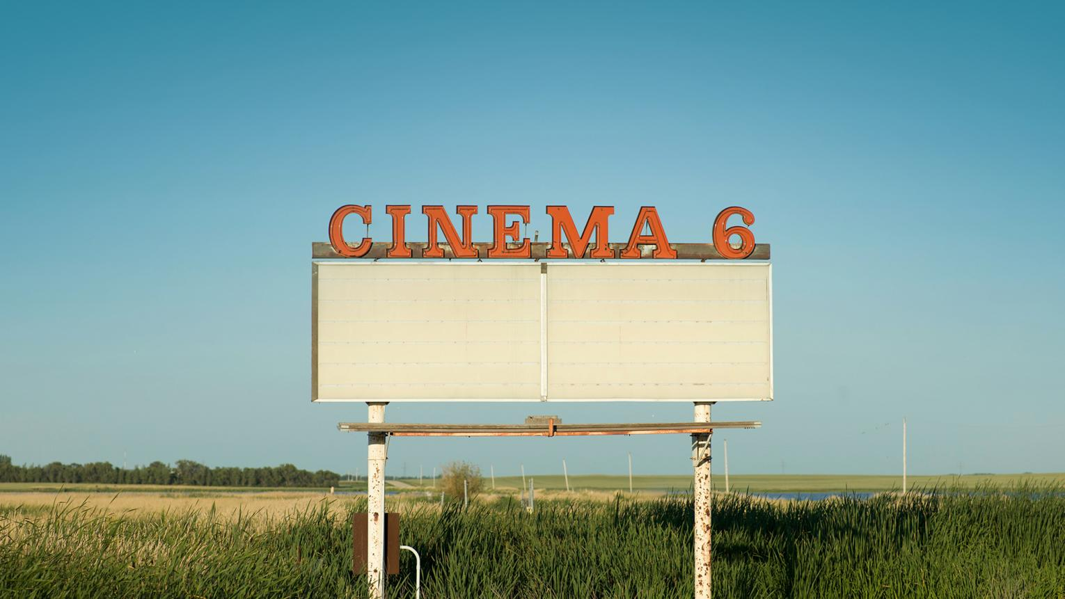 An orange cinema sign stands out against a blue sky.